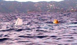 A wing of the recovered plane breaks the surface. The plane was floated using air bags. (Government House photo)