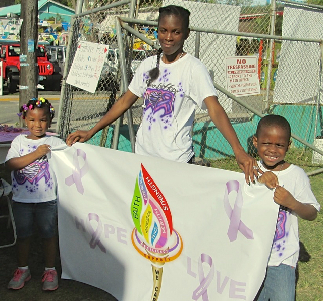 Ohanna Mitchell, 4, Onnika Gumbs, and KeMoy Joshua, 4, hold up their banner.
