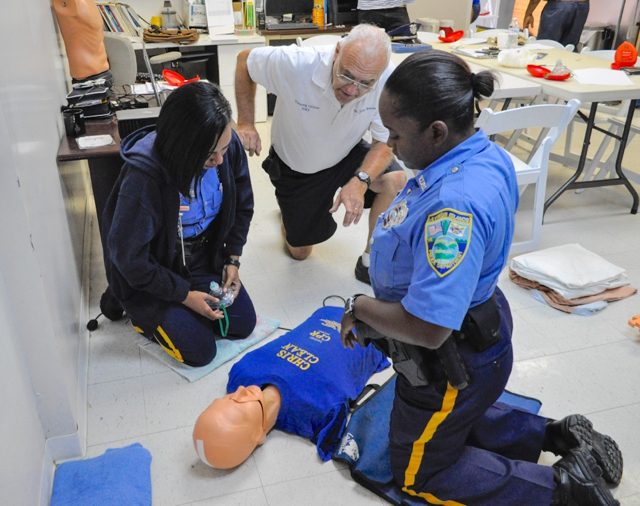 EMT Bob Malacarne explains CPR techniques to VIPD officers Yaniris Madera and Shennel Weekes.