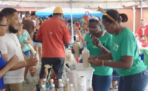 Tawana Nicholas and Jordan Albany pass out samples of coquito at the 2017 Coquit Festival. File photo)