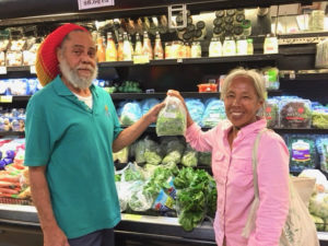 Starfish Market produce clerk Leslie Lambertis and Josephine Roller put a fresh bag of St. John-grown greens on the shelf.