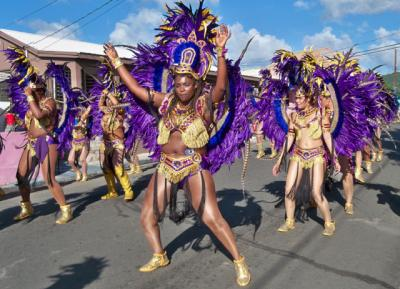 A colorful dance troupe marches down Fisher Street