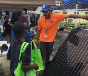 Pete Mottl explains how a solar panel creates electricity to Thora Henry Letang and her children.