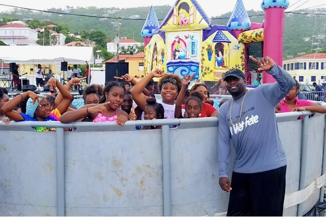 St. Thomas soca star BDJ, right, and a poolful of kids having fun in the water.