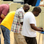 Voters fill in their ballots at the Gladys Abraham Elementary School Polling site inside UVI's Sports and Fitness Center.