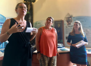 Meaghan Enright explains the Resilient Housing Initiative while Heidi Arnold and Celia Kalousek listen.