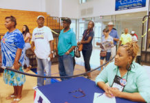 Polling Judge Donna Phillip, right, looks on as voters file into the UVI polling site.
