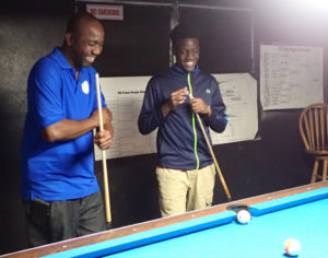 Billiards coach Jerome Anthony and champion Mahkeal Parris share a laugh as they talk strategy.