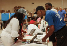 A pollworker hels a voter log in at the Lockhart polling site. (April Knight photo)
