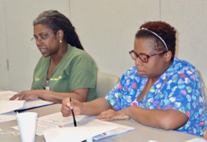 Dr. Olivine Anne Treasure and Faye John-Baptiste, registered nurse, discuss hospital operations Tuesday night. The two were the only board members present for the meeting, leaving the three short of a quorum.