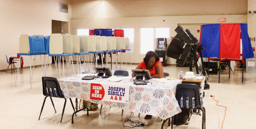 A Joseph Sibilly polling judge waits for voters at the Lockhart Elementary polling place on St. Thomas.
