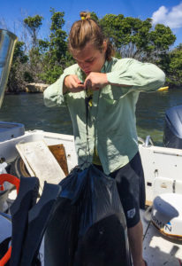 Volunteer Owen Clower weighs a bag of plastic trash on the garbage boat. (April Knight photo)