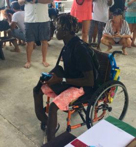 Wheelchair bound Fillemon Waikuwile receives his award.