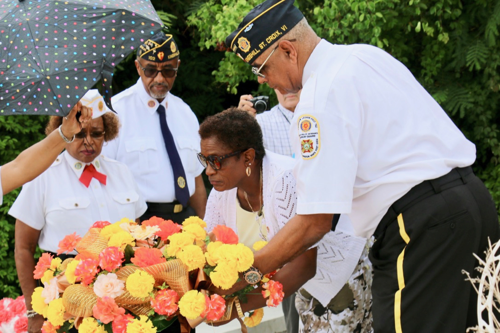 Ana Hernandez McIntosh places a wreath in honor of her husband, Gleston McIntosh and in remembrance all other veterans who have died. (Linda Morland photo)