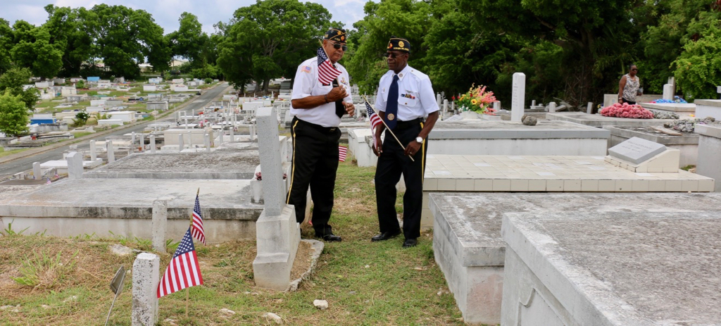 Bruce Gordon, 1St. Vice Commander and Ira Williams, 2nd Vice Commander of American Legion Enrique Romero Nieves Post No. 102 examine the new flags being placed on the graves of veterans in the Kingshill Cemetery. (Linda Morland photo)