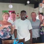 A group of cruise ship visitors surround chef/owner Christopher 'Naddy' Samuel at his Tail End Bar, Restaurant and Courtyard.
