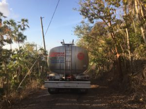 A water truck navigates loosely paved roads while delivering gallons of water to a V.I. resident. (Kelsey Nowakowski photo)