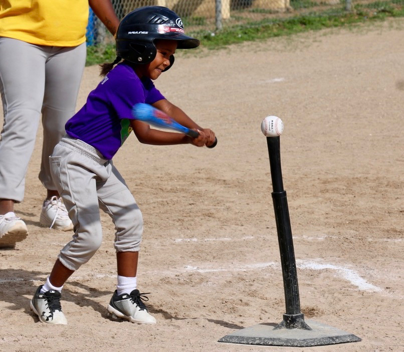 Five-year-old Ivaleeze Lampe takes a full swing at the teed-up baseball as she bats for the Diamond Dolls.