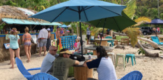 Visitors dine in the shade of an umbrella at Maho Crossroads. (Source photo by Amy Roberts)