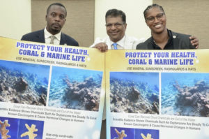 After the sunscreen bill was passed Tuesday by the Senate, Sen. Marvin Blyden, left, environmental advocate Harith Wickrema and Sen. Janelle Sarauw pose with sunscreen bill information. (Photo by Barry Leerdam for the V.I. Legislature)