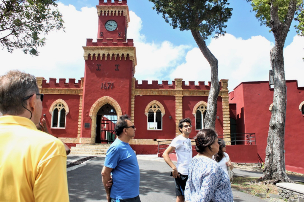 Gerard Sperry, left turned away from the camera, begins the tour at the historic site of Fort Christian where he relays pirate stories for patrons Bhushan Pandya, Ketan Pandya, Kavita Goel and Rashmi Pandya. (Source photo by Bethaney Lee)