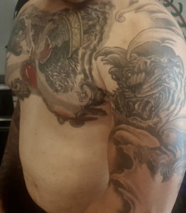 A customer displays his tattooed upper chest and arm. (Source photo by Denise Lenhardt-Benoit)