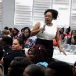 At a packed community meeting Thursday, Education Commissioner Racquel Berry-Benjamin details the department's plans to move three schools. (Source photo by James Gardner)