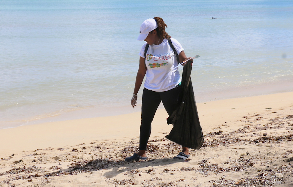Precious Laurent, one of the team from Cane Bay Cares, walks the sand looking closely for small, sharp objects. (Source photo by Linda Morland)