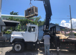 Michael Marsh uses his crane to install a generator at the St. John shelter. (Source photo Amy Roberts)