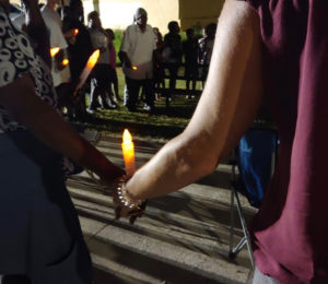 Community members hold hands and candles in remembrance of those who have died violently in their community. (Source photo by Shaun Pennington)