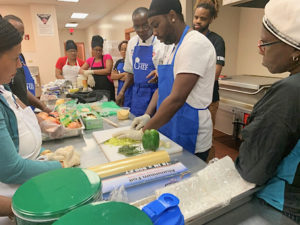 Chef Larry Nibbs of St. Thomas, center, offers kitchen tips and instruction on food prep. (Photo submitted by Government House)