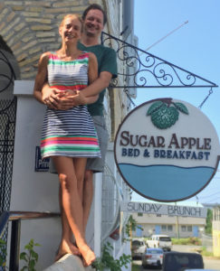 Corina Marks and Ryan Flegal, new owners of the Sugar Apple Bed and Breakfast pose with the new sign. (Source photo by Susan Ellis)