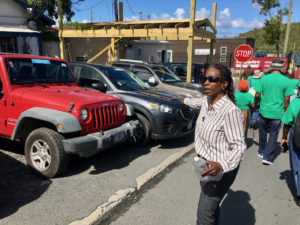 Edithrose Jennings points to a sidewalk blocked by parked cars. (Source photo by Amy Roberts)