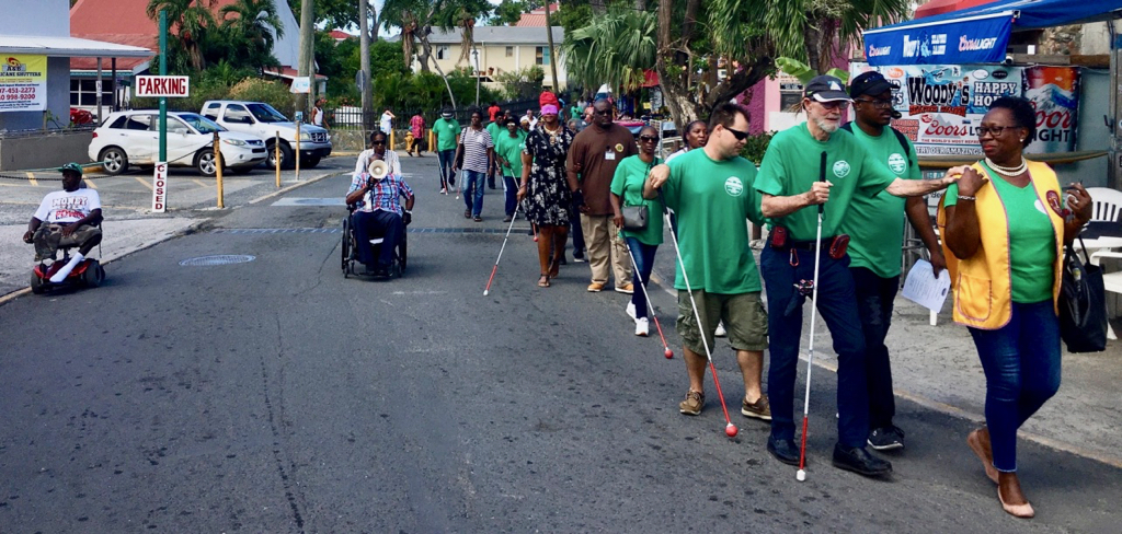 The White Cane Day celebration treks through Cruz Bay. The march up the hill to the roundabout is a challenge for those in wheelchairs. (Source photo by Amy Roberts)