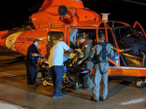 The crew of a U.S. Coast Guard MH-65 Dolphin helicopter assists a crew member of the Marella Eplorer 2 Cruise ship. The crew member had been stricken by a heart attack at sea and was medevaced to St. Croix, where he was treated at the Juan F. Luis Hospital. (U.S. Coast Guard photo)