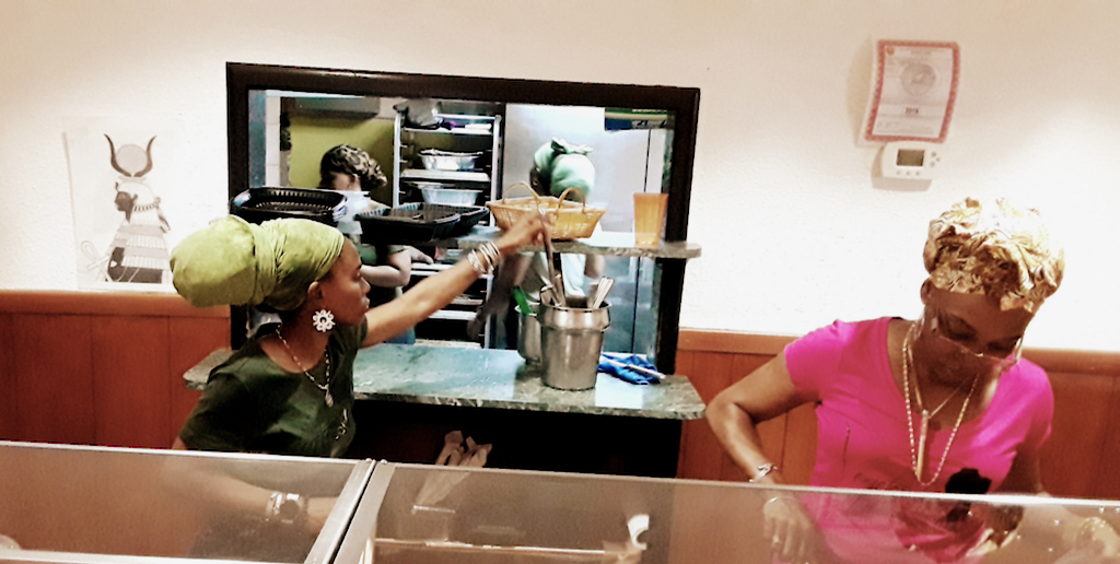 Isumyah Schrader's daughters, Ama and Amibala, serve customers. (Source photo by Darshania Domingo)