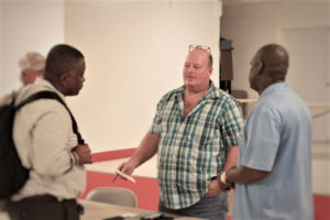 Julian Magras, center, speaks with Sens. Athneil Thomas, left, and Stedmann Hodge. (Source photo by Bethaney Lee)
