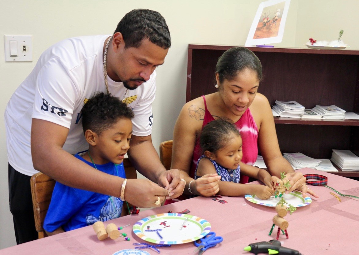 The entire Encarnacion family participated in an afternoon of creating Christmas ornaments. Christopher stands to help his son, Jahzari. Rickysha holds Baejah on her lap as they work on a reindeer. (Source photo by Linda Morland)