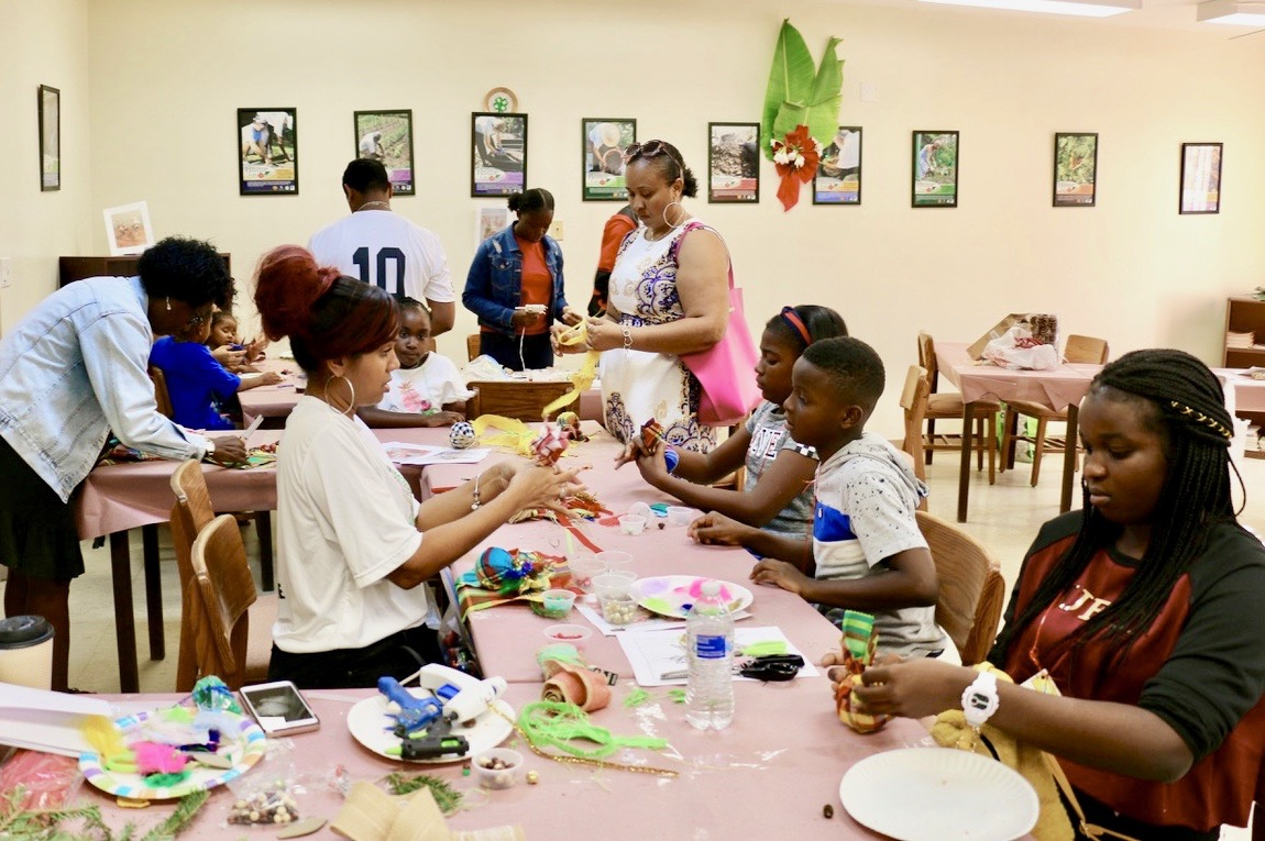 Grace King, 4-H Ambassador (center) helps as children gather at her table to work on ornaments using bright madras fabric. (Source photo by Linda Morland)