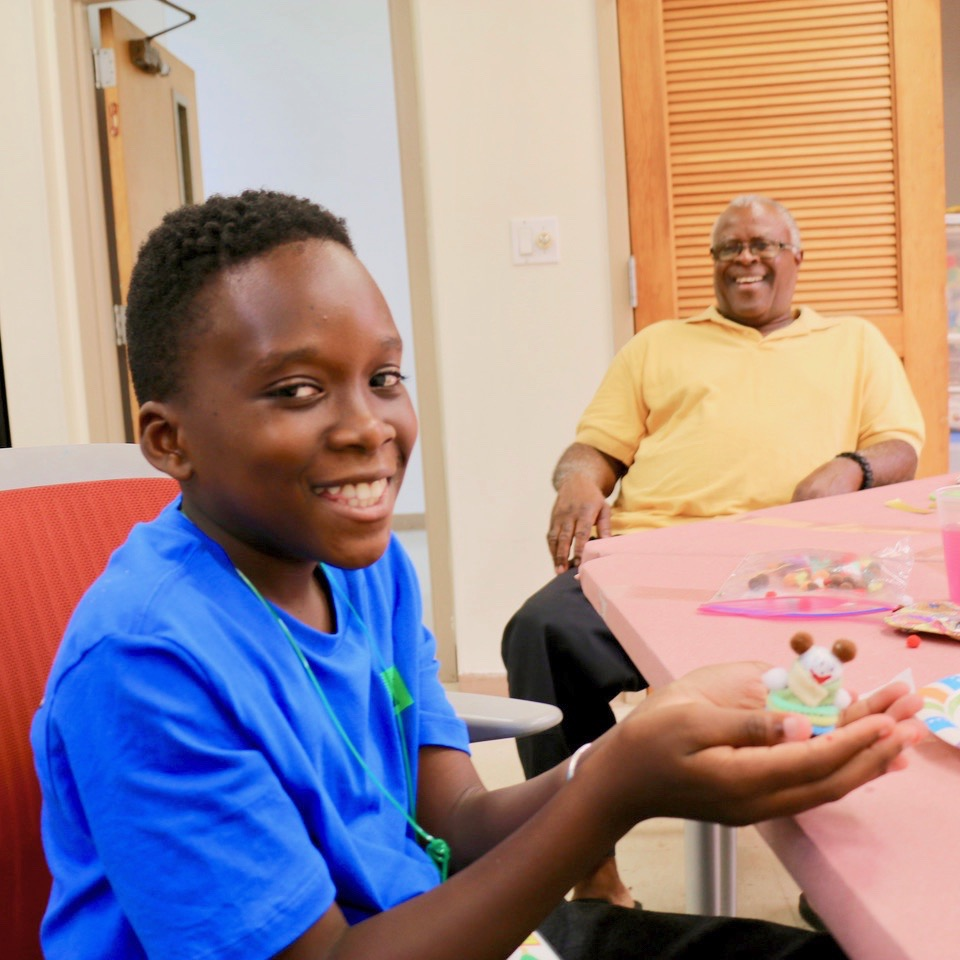 Joey Swanson, Jr. holds a freshly made Christmas panda ornament as his grandfather, Rodney Thomas enjoys the fun in the background. (Source photo by Linda Morland)