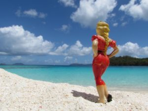 Image from 'On These Shores' – photograph of figurine in red dress on the beach, by Janet Cook-Rutnik. (Submitted photo)