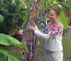Volunteer Lise Sorensen with one of the many trees and bushes decorated on the grounds. (Source photo by Don Buchanan)