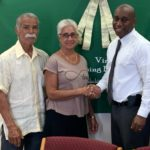 From left, J.T. Torres and Angela Morales are congratulated by VIHFA director Daryl Griffith. (Photo provide by VIHFA)