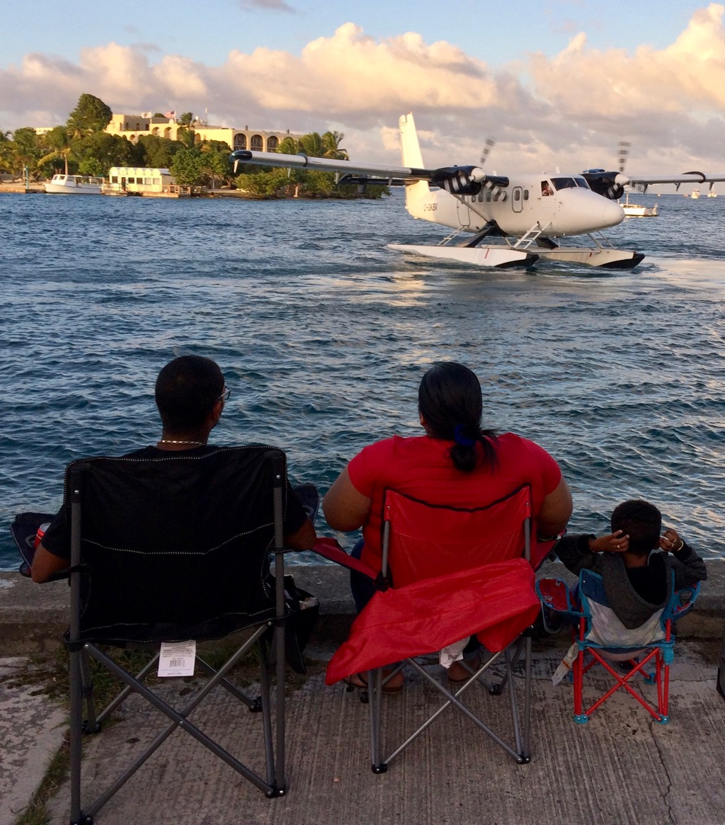 A Seaborne plane maneuvers in the harbor as a well-situation family watches. (Source photo by Don Buchanan)