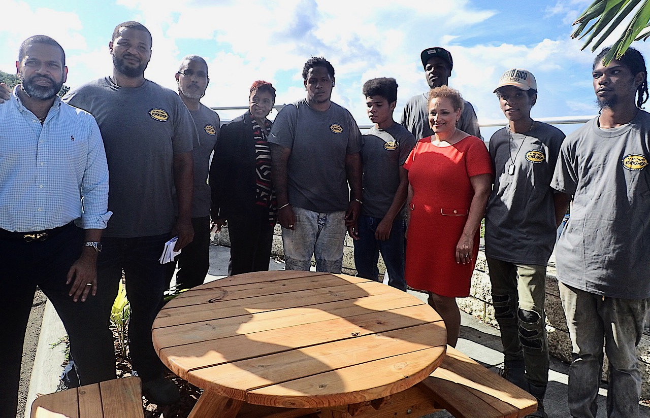 From left, Troy de Chabert Schuster, Derrick Venzen, Eddie Martinez, Alicia Georges, RaySanderson Jr., Dursha Gruhars, Josiah Keels, Jo Ann Jenkins, Christopher Mitchel and Isaiah Moore admire the picnic table designed and built by My Brothers Workshop. (Source photo by Susan Ellis)