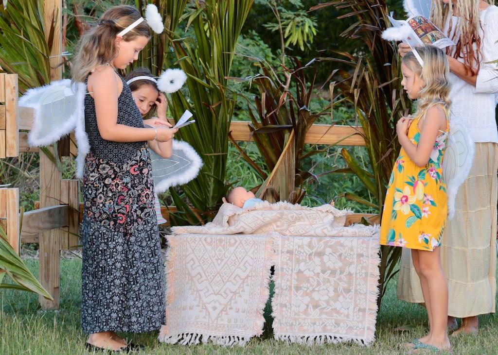 Lena Kammerzelt, Madison Locher, Nora Kammerzelt, as angels, gather round the manger. (Source photo by Linda Morland)