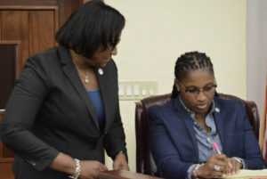 Sens. Donna Frett-Gregory and Janelle Sarauw discuss the VIVIS bill, which they co-sponsored. (Photo by Barry Leerdam, USVI Legislature)