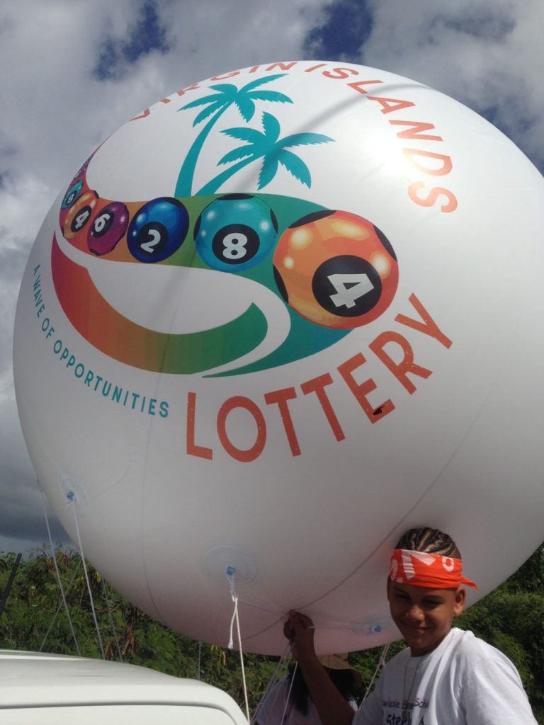 Jadym Arroya's mother works at the V.I. Lottery, which got him a ride in the parade along with a giant ball. (Source photo by Don Buchanan)