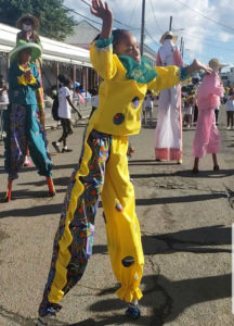 A young moko jumbie gets the feel of the stilts in the parade. (Source photo by Melody Rames)
