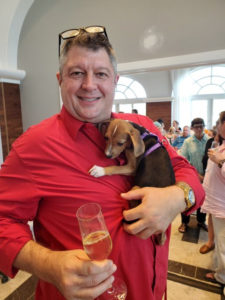 Jim Hines, General Manager at Bellows International, smiles while holding a puppy in one arm and a glass in the other. (Photo submitted by Annette Zachman)